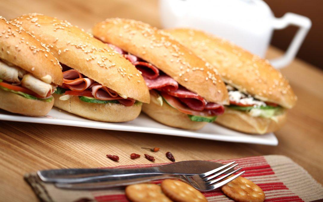Row of four deli sub sandwiches
